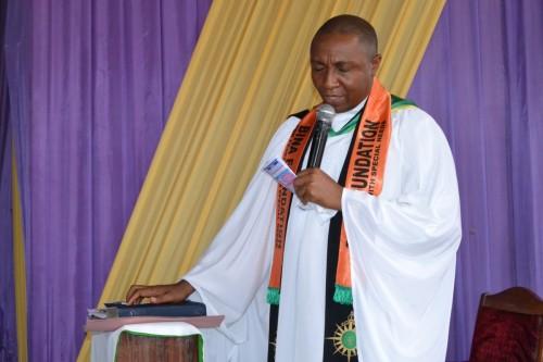 Resident Priest, Revd. Eneasato thanks God for Bina Foundation