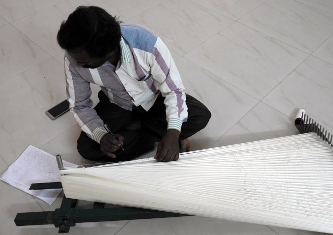 A weaver making the design