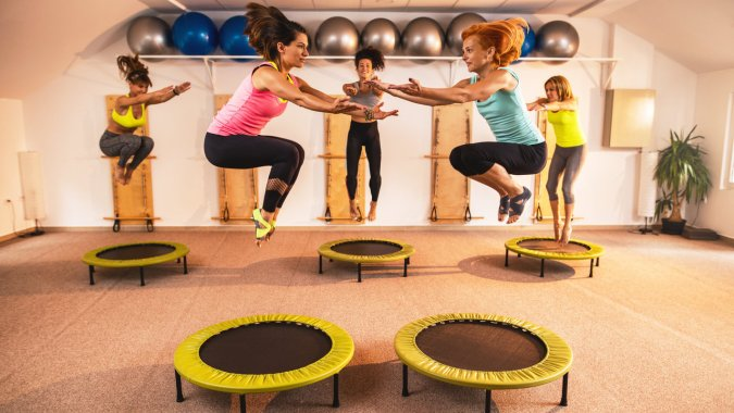 Athletic women exercising in health club and jumping high up on mini trampolines.