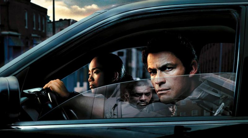 Detectives from The Wire sit in a car with a nemesis reflected in the window