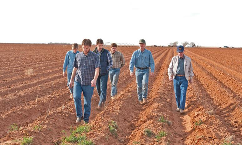 Eddie Bingham and son, Cliff Bingham, walking in their farm field with grandsons, Clint, Kyle, Blake, and Nathan.