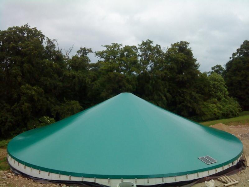 Zdjęcie przedstawiające zielony, stożkowy zbiornik na gnojowicę
