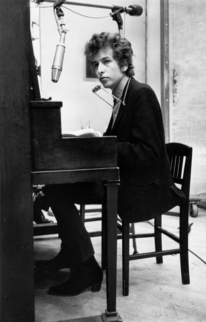 Bob Dylan plays piano with a harmonica around his neck while recording his album 'Highway 61 Revisited' on January 13-15, 1965, in Columbia's Studio A in New York City