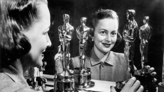 Olivia de Havilland smiling with her two Oscars, 1950s