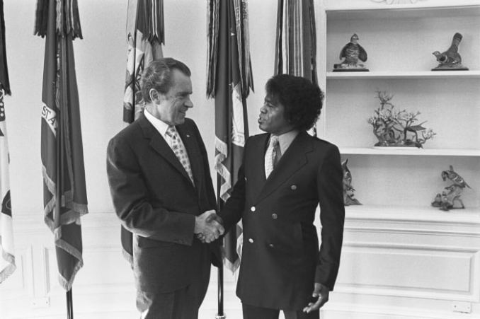 Richard Nixon shakes hands with James Brown in the White House's Oval Office on October 10, 1972