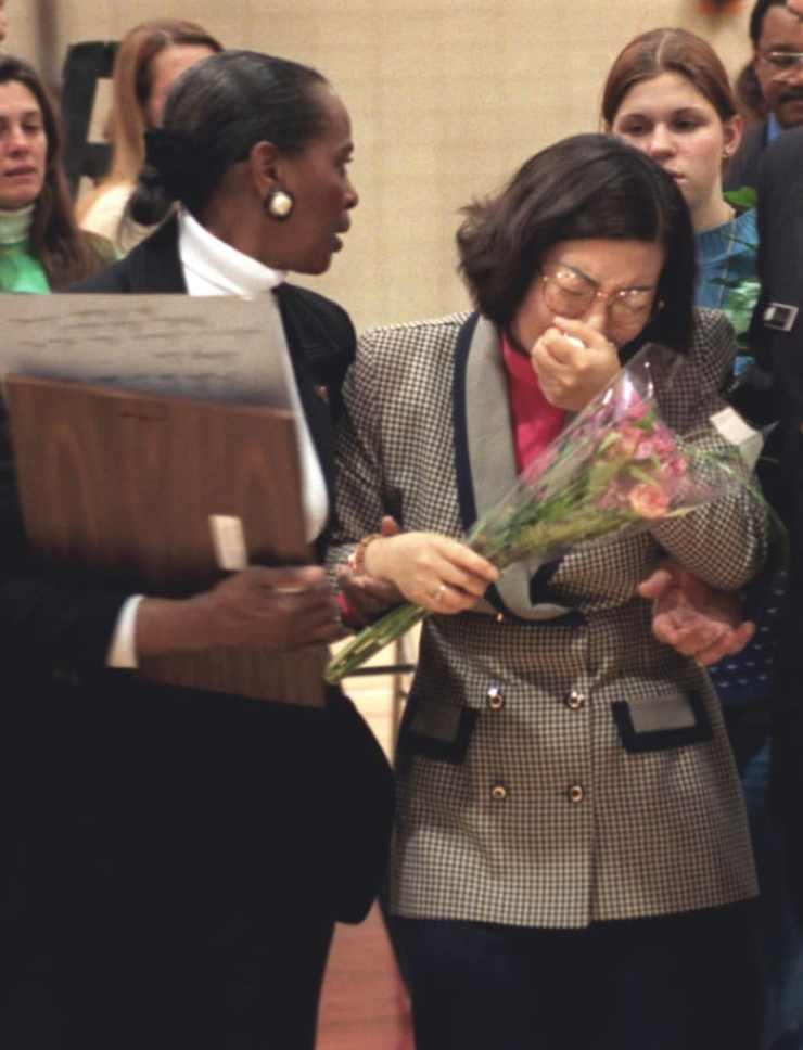 Youn Kim (r), mother of Hae Min Lee, is escorted from her daughter's Memorial Service by guidance counselor Gwen Kellam, on March 11, 1999, in Baltimore, Maryland