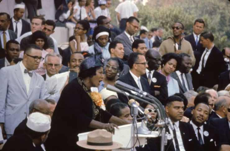 Mahalia Jackson sings at the March on Washington on the steps of the Lincoln Memorial, Washington, DC, on August 28, 1963. Sitting at lower right is civil rights leader Martin Luther King Jr.