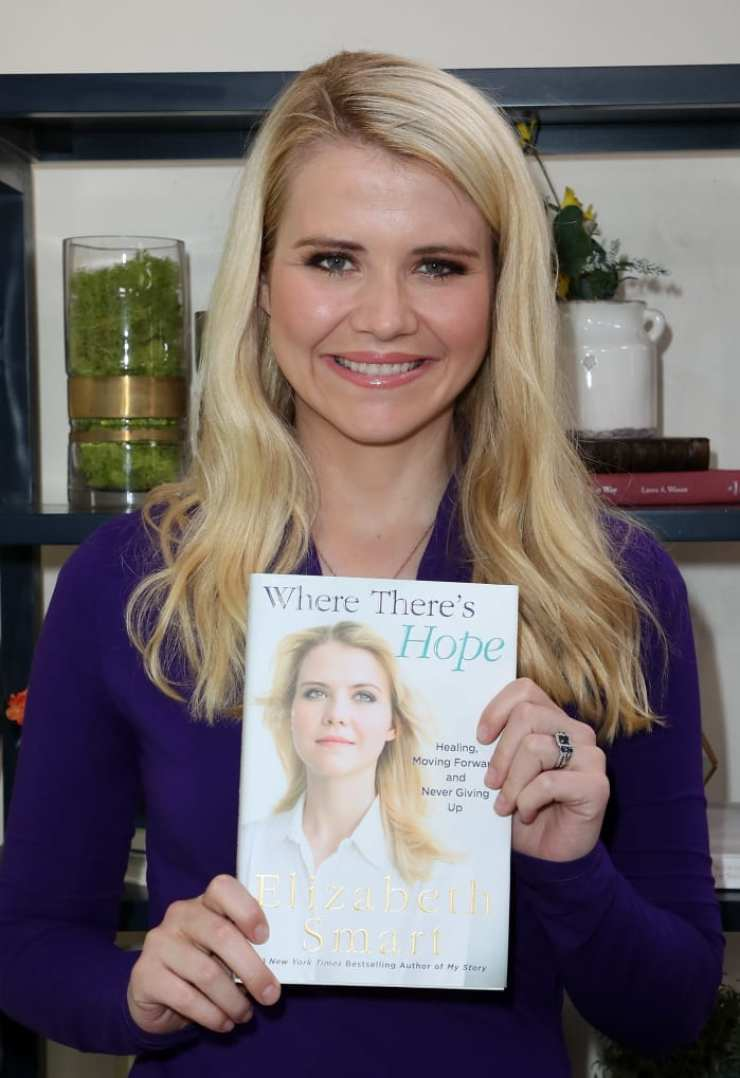 """Elizabeth Smart holding her book """"Where There's Hope"""" on April 6, 2018 in Universal City, California"""