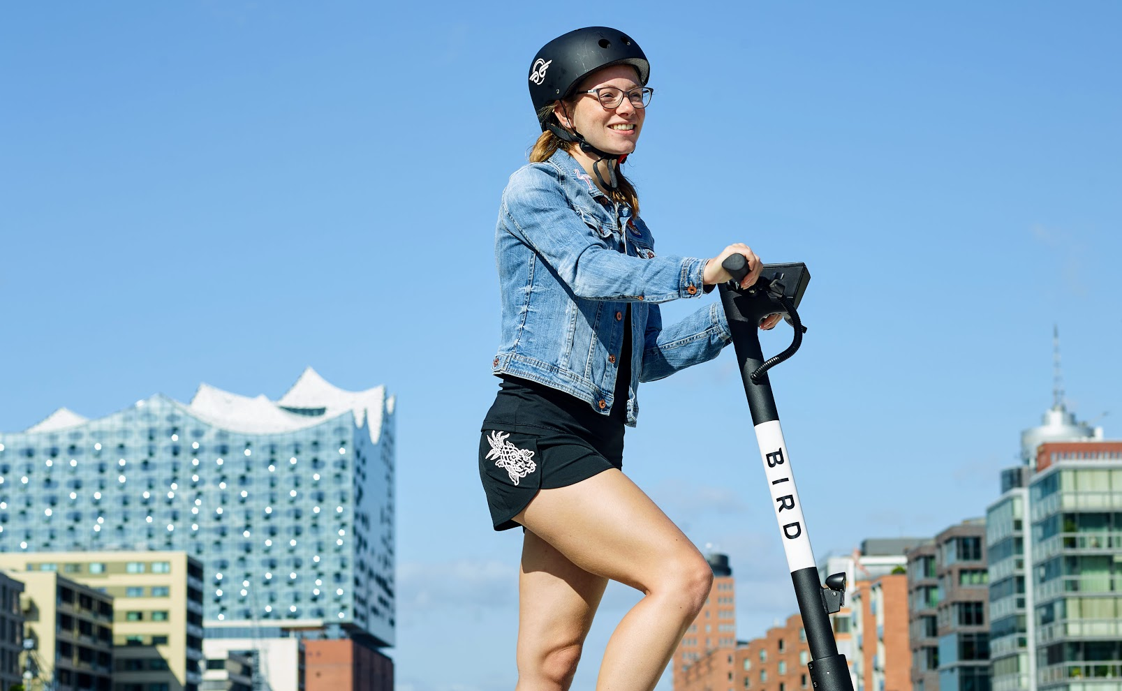 Girl wearing Bird helmet stands atop Bird One electric scooter with city buildings in background
