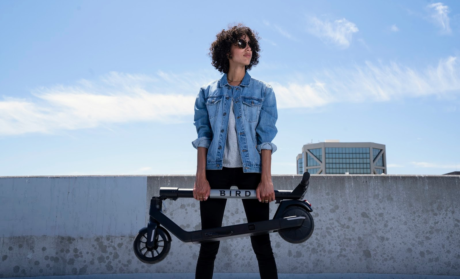 Young woman holding Bird Air electric scooter on a rooftop on a sunny day.