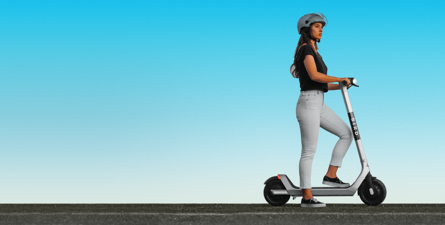 Woman standing on Bird scooter, looking into the distance