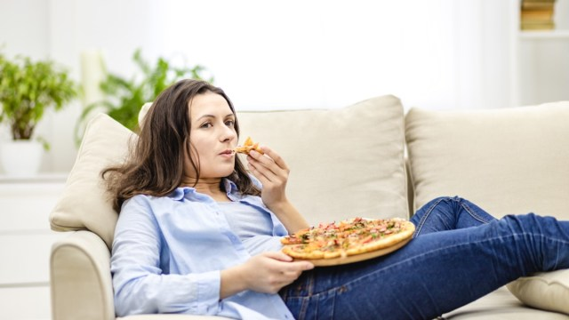 Woman is chewing pizza while lying on the white sofa.  She watches television programs on a blurred background.