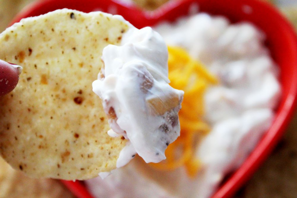closeup of bacon ranch cheddar dip on a chip with bowl in background 1
