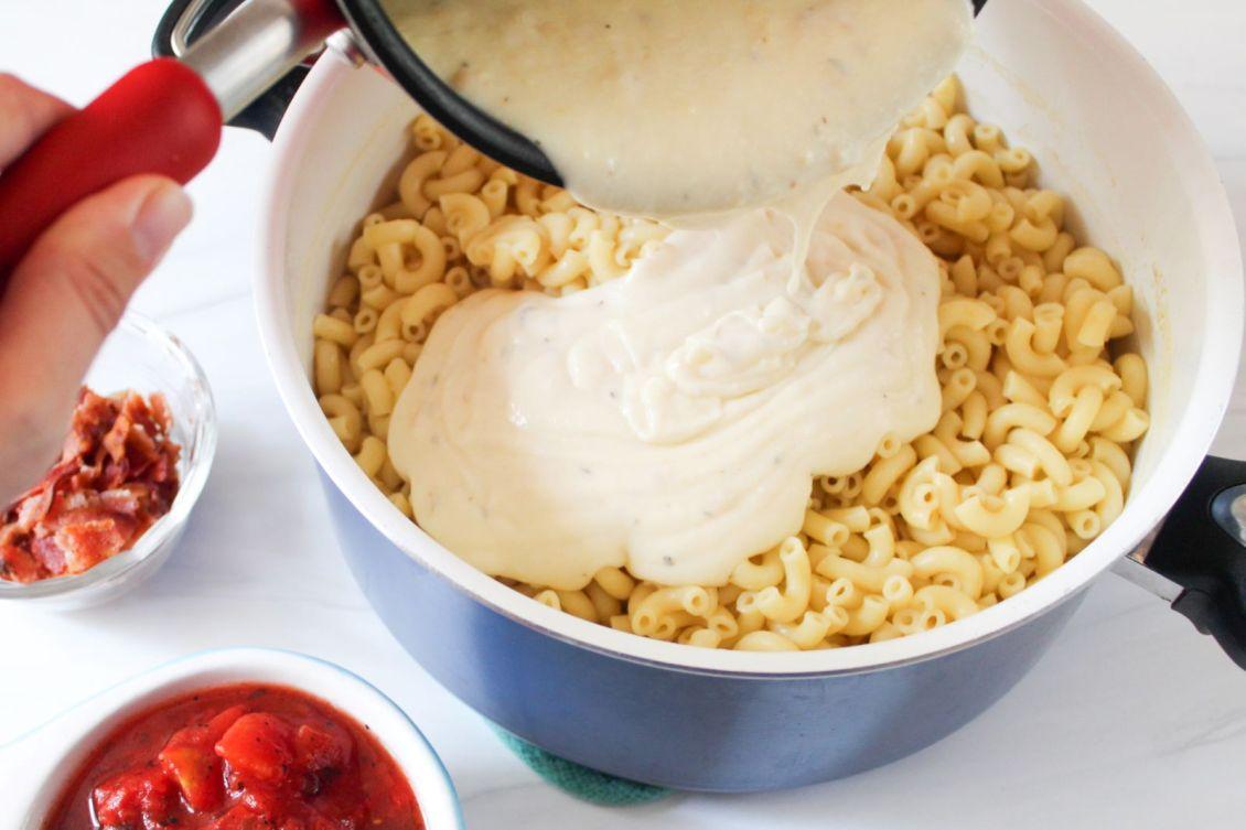 pour gouda white cheddar cheese sauce into macaroni 1