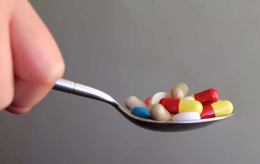 Spoon containing supplement pills