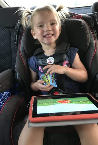 A picture of Angela's daughter strapped into a car seat with a tablet in her lap and a huge smile on her face.