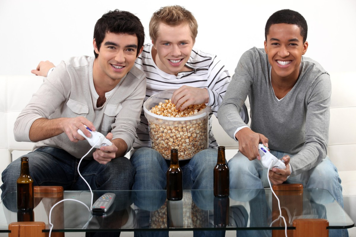 Three friends playing video games while drinking beer.