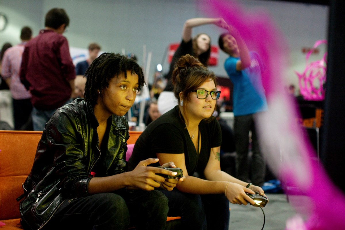 """** PHOTO MOVED IN ADVANCE AND NOT FOR USE - ONLINE OR IN PRINT - BEFORE DEC. 14, 2014. ** FILE — Tion Burton and Elaine Gomez, right, play a video game at the Electronic Entertainment Expo in Los Angeles, June 12, 2014. Where video games once had external enemies, the biggest threat to the culture now seems to come from within, in the form of the harassment of women gamers and creators, and the uproar over """"GamerGate."""" (Emily Berl/The New York Times)"""