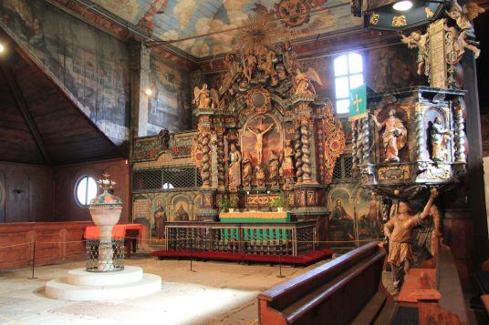 Ova crkva ima izniman interijer s oslikanim zidovima i rezbarijama koje se smatraju najljepšima od svih 5 artikularnih crkava u Slovačkoj. Novac za njezinu izgradnju je sakupljan diljem Europe, od Švedske do Danske. Arhtekt je bio Juraj Müttermann iz Popradua, a crkva je svojom duljinom od 34.68 i širinom od 30.31 m, te sa 6 bočnih korova, mogla primiti preko 1500 vjernika; najviše od svih drvenih crkava. Slike na svodu su započete 1717. godine, ali su završene tek desetljećima kasnije. One prikazuju plavo Nebo s 12 apostola, 4 evanđelista i Sveto Trojstvo iznad oltara. Ján Lerch je izrezbario oltar od 1718.-28., a orgulje Vavrinec Čajkovský od 1717.-20. koje je proširio Martin Korabinský 1729. godine.