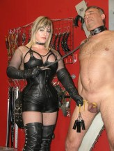 Blond Dominatrix in Leather Corset and Thigh High Boots Degrades a slave