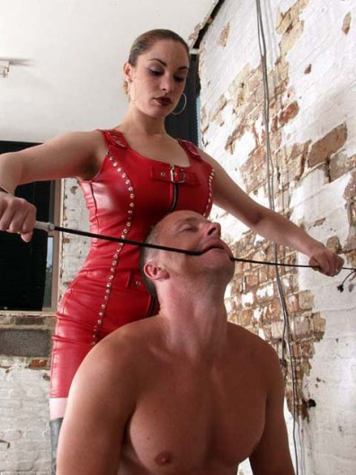 Domina in Red Leather Humiliates a male slave