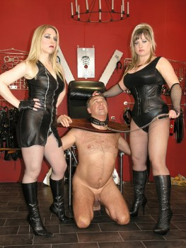 Two Awesome Mistresses Whip and Trash a helpless male slave in Stocks