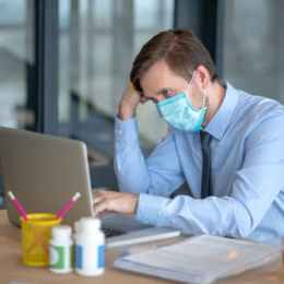 After catching cold. Hard-working office worker wearing protective mask after catching cold
