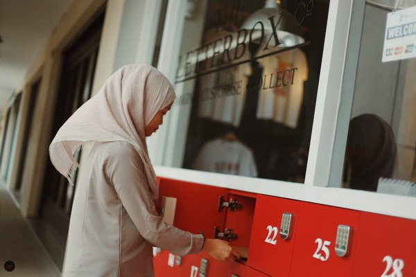 A staff of Letterbox checking out the store's unique collection system designed by Wa'iz. Customers are given a pin so they can collect their items at any time of the day. Picture: Hj Safwan