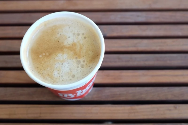 An above view of a latte in a paper cup sitting on a wooden slatted surface.