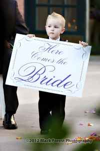 Here comes the bride sign held by ring bearer
