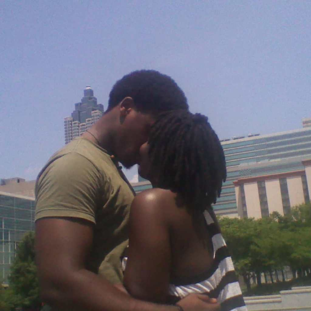 African-American Couple kissing in the park with city buildings in background