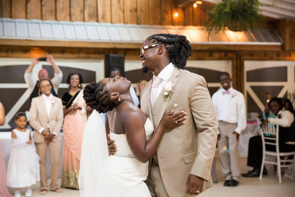 African-American woman and man dancing at wedding. Woman is in white wedding dress and man is in tan suit holding the woman by the waist.