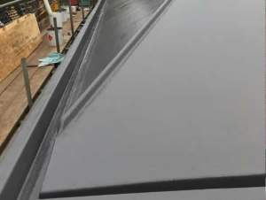 Slate grey Topcoat finish to roof area and gulleys. GRP FIbreseal Roof by Blackpool Industrial Roofing.