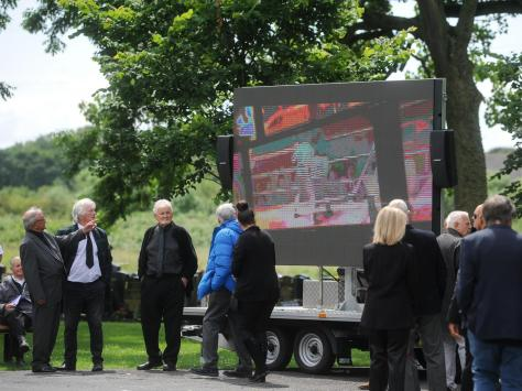 A projector outside the crematorium played clips of Brian in his boxing days