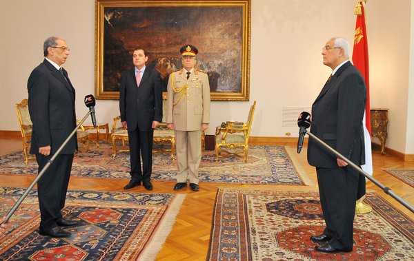 Newly-appointed prosecutor general Hisham Barakat, left, is sworn in in front of interim president, Adli Mansour, right, at the presidential palace in Cairo on Wednesday.