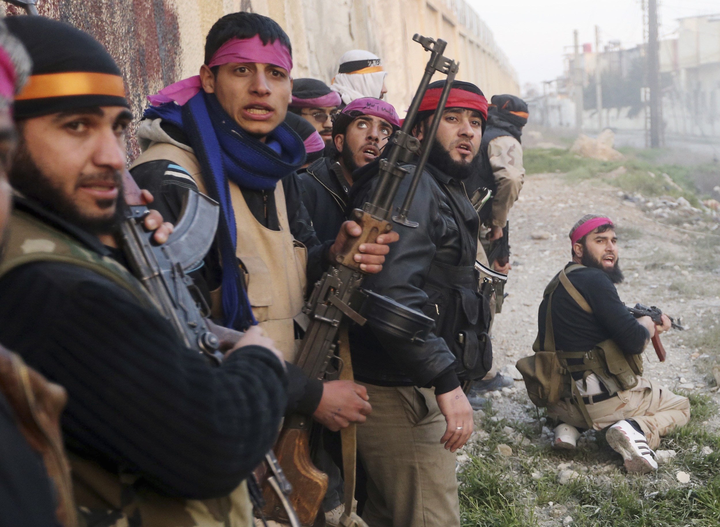 File photo of Free Syrian Army fighters taking cover as they prepare to join an attack on a Syrian Army base in Damascus