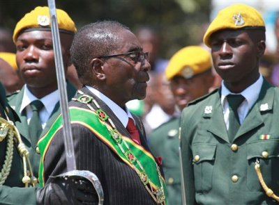 """In this file photo taken Tuesday, Sept. 17, 2013 Zimbabwean President Robert Mugabe inspects the guard of honor during the opening of the first session of the eighth Parliament of Zimbabwe in Harare.  Zimbabwe's longtime President Robert Mugabe says he doesn't want anyone to be fooled by his impeccable Western style of dress and his precise, teacherly use of English: He is African through and through. """"I am not British, I am not a colonial product because I am a complete Zimbabwean, """" he told graduates at Great Zimbabwe University near the remains of the 13th Century walled city, for which Zimbabwe, the former colony of Rhodesia, is named. (AP Photo/Tsvangirayi Mukwazhi-file)"""
