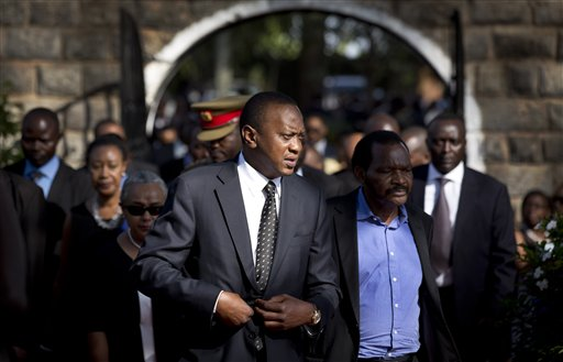 In this Friday, Sept. 27, 2013 file photo, Kenya's President Uhuru Kenyatta, center-left, arrives for the burial ceremony of his nephew Mbugua Mwangi and Mwangi's fiancee Rosemary Wahito, who were both killed in the Westgate Mall terrorist attack, at the burial site in the village of Ichawara, Kenya. A new poll released Thursday, Nov. 14, 2013 by Ipsos Synovate says two out of three people in Kenya want to see their president report to the International Criminal Court to respond to charges of crimes against humanity. (AP Photo/Ben Curtis, File)
