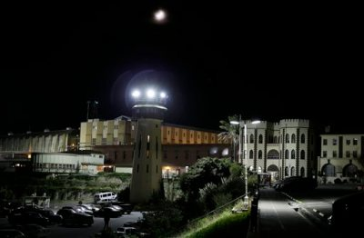 In this Thursday, Nov. 7, 2013 photo, a moon shines over San Quentin State Prison in San Quentin, Calif. The Last Mile program trains selected prisoners for eventual employment in a paid internship program within the Silicon Valley technology sector. Through twice-weekly sessions at the prison over a six-month period, the program provides information and practical experiences to increase knowledge and awareness about the role of social media, build skills in relevant areas for employment in the high-tech sector and foster confidence and a sense of hope that they can succeed as free men. (AP Photo/Eric Risberg)
