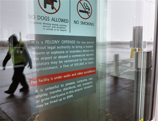 A security officer walks near a notice prohibiting marijuana possession at Denver International Airport, Monday, Jan. 27, 2014. (AP Photo/Brennan Linsley)
