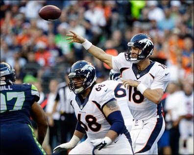FILE - In this Aug. 17, 2013, file photo, Denver Broncos quarterback Peyton Manning (18) passes as Zane Beadles (68) blocks in the first half of a preseason NFL football game against the Seattle Seahawks in Seattle. The two teams are slated to meet in Super Bowl XLVIII on Sunday, Feb. 2, 2014, in East Rutherford, N.J. (AP Photo/Elaine Thompson, File)