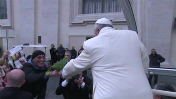 In this image made from video distributed by CTV,  a man offers his parrot to Pope Francis during his tour through the crowd in St. Peter's Square, part of his weekly general audience at the Vatican, Wednesday, Jan. 29, 2014. (AP Photo/CTV)