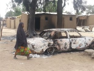 In this image taken with a mobile phone, a muslim woman walk past a burnout car and a house following an attack by  suspected Islamic extremists in Kawuri, Maiduguri, Nigeria, Tuesday, Jan. 28, 2014. (AP Photo/Jossy Ola)
