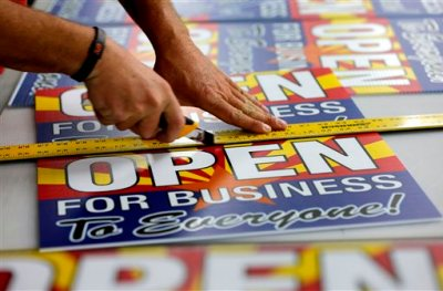 """Tom Cushing, a production expert at Fast Signs, cuts down a sheet of anti-Senate Bill 1062 signs that read """"Open For Business To Everyone"""", Wednesday, Feb. 26, 2014 in Phoenix. Arizona Gov. Jan Brewer will hold a series of private meetings with opponents and proponents of legislation adding protections for people who assert their religious beliefs in refusing service to gays. Brewer spokesman Andrew Wilder says the governor will spend Wednesday gathering information about Senate Bill 1062 as she considers signing it into law or a veto. She has until Saturday to act. (AP Photo/Matt York)"""
