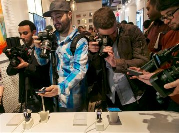 Photographers swarm around a Samsung Galaxy S5 smartphones, left,  and Samsung Gear 2's at the Samsung Galaxy Studio, in New York,  Monday, Feb. 24, 2014. (AP Photo/Richard Drew)