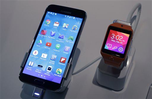 A Samsung Galaxy S5 smartphone, left,  and a Samsung Gear 2 are displayed at the Samsung Galaxy Studio, in New York,  Monday, Feb. 24, 2014. (AP Photo/Richard Drew)