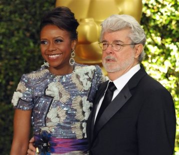 In this Nov. 16, 2013 file photo, filmmaker George Lucas and his wife Mellody Hobson are seen on the red carpet at the 2013 Governors Awards in Los Angeles. The University of Chicago said Tuesday, Feb. 25, 2014, that Lucas and Hobson are donating $25 million to the prestigious private school. The grant from The George Lucas Family Foundation will pay for a new arts hall at the university's Laboratory Schools.(Photo by John Shearer/Invision/AP)