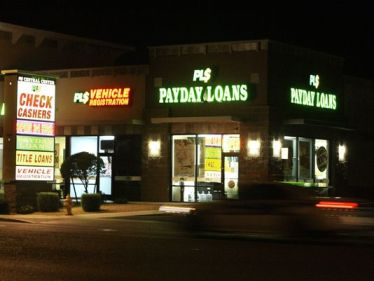 Neon signs illuminate a payday loan business. Payday loan borrowers often roll over their loans and wind up paying more in fees than they borrowed, the Consumer Financial Protection Bureau warns in a report out Tuesday. (Photo: Ross D. Franklin AP)