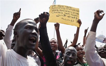 """A group of South Sudanese chant at a demonstration held in support of President Salva Kiir and against """"foreign encroachment"""" in Juba, South Sudan Monday, March 10, 2014. Arabic on placard reads """"No foreigners are allowed to intervene"""". (AP Photo/Mackenzie Knowles-Coursin)"""