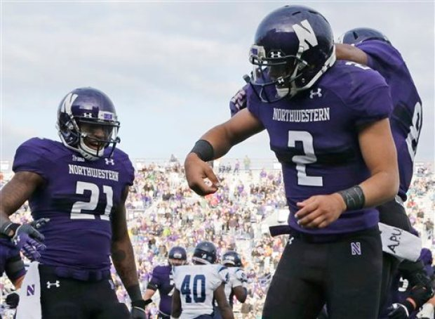 """In this Sept. 21, 2013 file photo,  Northwestern quarterback Kain Colter (2) wears APU for """"All Players United"""" on wrist tape while celebrates with running back Stephen Buckley (8) and wide receiver Kyle Prater (21) after scoring a touchdown in an NCAA college football game against Maine in Evanston, Ill.  The decision to allow Northwestern football players to unionize raises an array of questions for college sports. Among them, state schools vs. public schools, powerhouse programs vs. smaller colleges. (AP Photo/Nam Y. Huh, File)"""